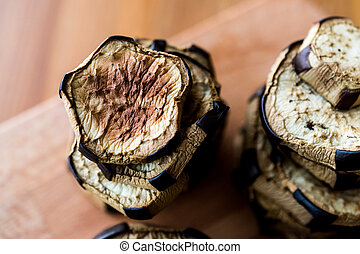 Stack of Fried Eggplant on wooden surface.