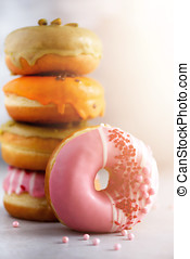 Stack of glazed colorful assorted donuts with sprinkles on grey cement background. Copy space. Sweet doughnuts for kids