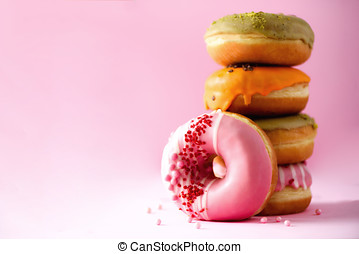 Stack of glazed colorful assorted donuts with sprinkles on pink background. Copy space. Sweet doughnuts for kids