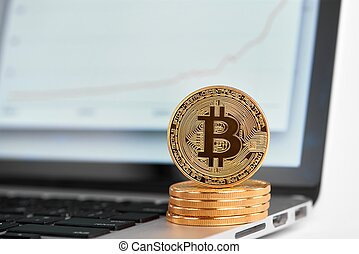 Stack of golden bitcoins with one bitcoin on its edge standing on laptop with financial chart on its screen