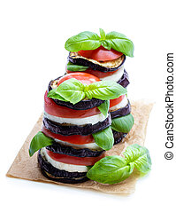 Stack of grilled eggplant with tomato and cheese isolated on white
