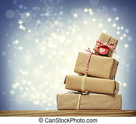 Stack of handmade gift boxes over snowing night background