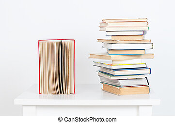 Stack of hardback books and old open book on white wall background. Search for relevant necessary information.
