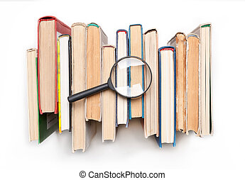 Stack of hardback books with magnifying glass isolated on white background, top view. Search for relevant and necessary information.
