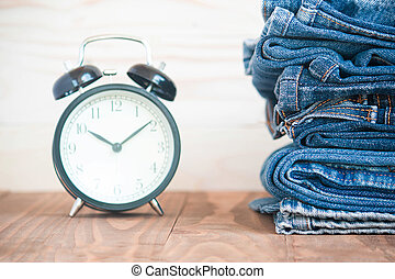 Stack Of Jeans And Classic Timepieces On Old Wood Flooring, Fashion Concept With Time