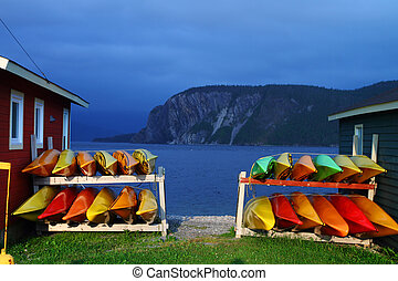 Stack of kayaks - Stack of multicolored kayaks on the shore...