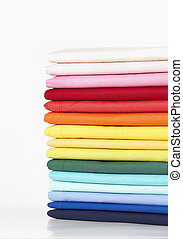Stack of coloured linens isolated on white background