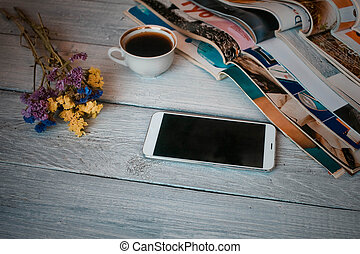 Stack of magazines and the smartphone on a white wooden background