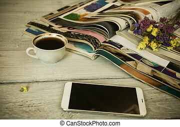 Stack of magazines, cup about coffee and the smartphone on a white wooden background