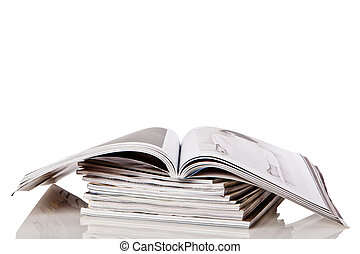 Stack of magazines top one open isolated on white background...