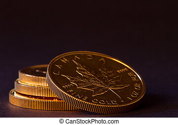 Stack of maple leaf gold coins - Three gold coins in a...