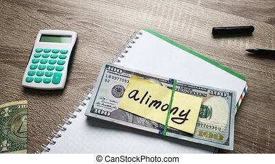 Stack of money for pay alimony on wooden table
