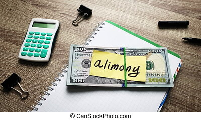 Stack of money for pay alimony on wooden table.