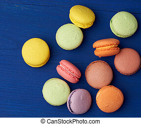 stack of multi-colored round baked macarons cakes on a blue wooden background