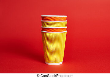 Stack of multicolored paper disposable cups for hot drinks on a red background with copy space.