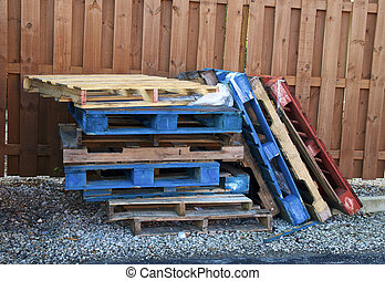 stack of multicolored wood forklift pallets outside