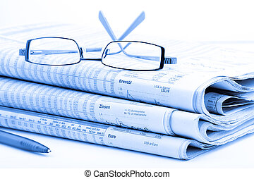 Stack of newspapers and glasses blue toned