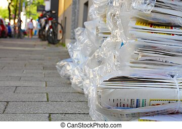 Stack of newspapers on a sidewalk