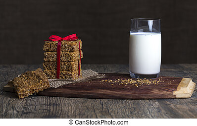 Stack of oatmeal crunchy cookies and milk in background
