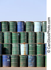 oil barrels - stack of oil barrels against a  blue sky