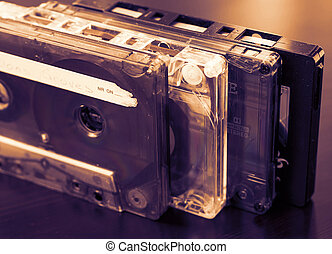 Stack of old audio tapes on a dark wooden background close up