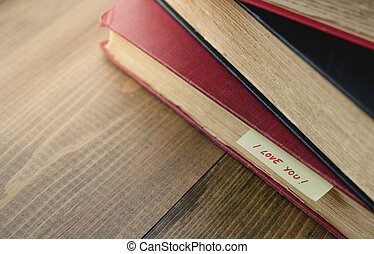 Stack of Old Book with Bookmarks I love you writing on Wooden Background