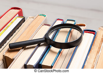 Stack of old hardback books with magnifying glass. Search for relevant and necessary information.