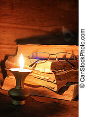 old tattered book on a wooden table lighted candle and glasses