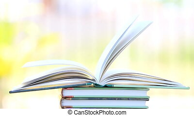 Stack of open book in wind, green garden background.