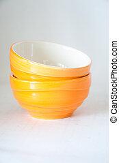 Stack of orange ceramic dishes on white background
