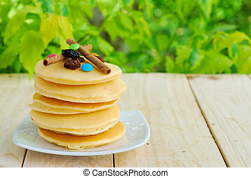 Stack of pancakes and syrup in plate on wooden table with green