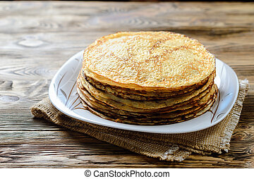Stack of pancakes on wooden table.