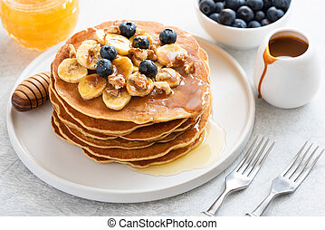 Stack of pancakes with banana, blueberries, walnuts, honey and caramel sauce
