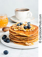 Stack of Pancakes With Banana Blueberry Walnuts and Honey