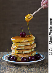 Stack of pancakes with berries and honey dripping over