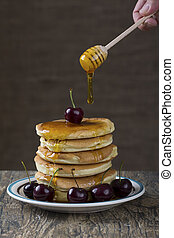 Stack of pancakes with berries and honey dripping over it