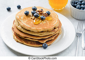 Stack of pancakes with blueberries, walnuts and honey on white plate.