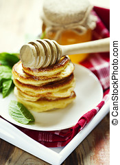 stack of pancakes with honey