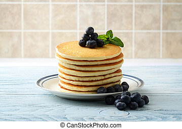 stack of pancakes with pile of blueberries on plate