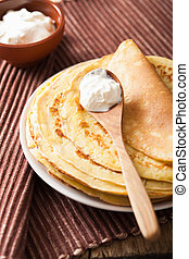 stack of pancakes with sour cream