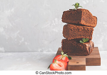 Stack of pieces of homemade dark chocolate brownie with strawberries on a wooden board.