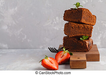 Stack of pieces of homemade dark chocolate brownie with strawberries on a wooden board, copy space, copy space.