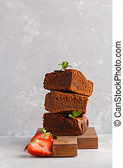 Stack of pieces of homemade dark chocolate brownie with strawberries on a wooden board, copy space.