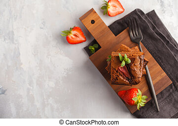 Stack of pieces of homemade dark chocolate brownie with strawberries on a wooden board. Top view, copy space.