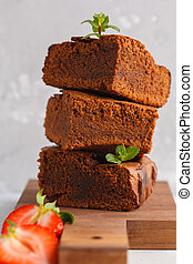 Stack of pieces of vegan homemade dark chocolate brownie with strawberries on a wooden board.