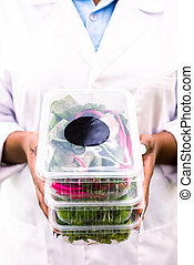 Stack of plastic containers with fresh green leaves held by African female