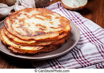 Stack of potato pancakes on a wooden table. In the ...