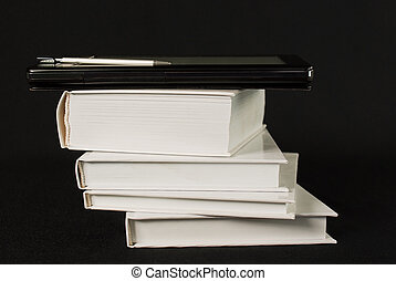 Stack of printed books with electronic book reader on black background