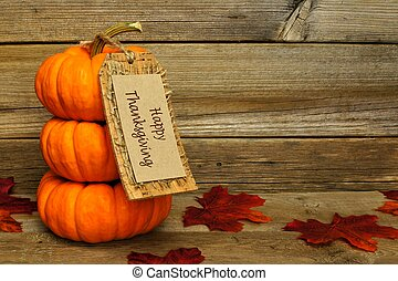 Stack of pumpkins with Happy Thanksgiving tag over wood