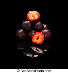 Stack of purple plums isolated on black